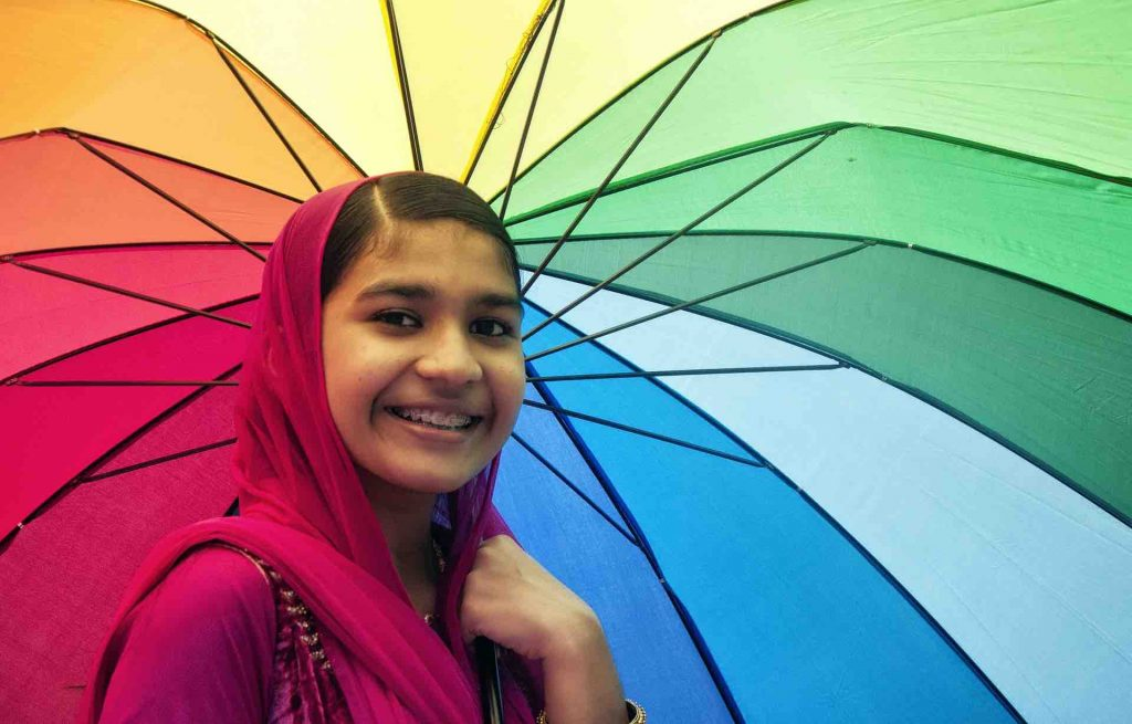 Woman with braces smiling in front of a colorful umbrella