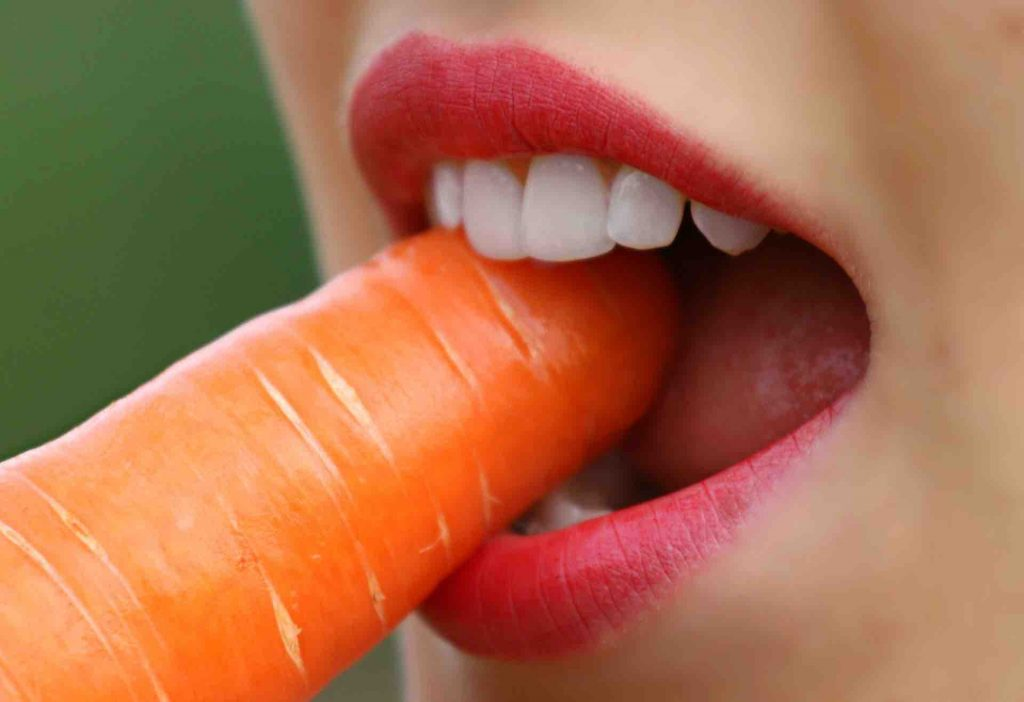 Woman biting a carrot